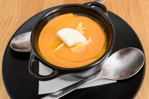 High angle close up of tomato soup in a black bowl.の写真素材 [FYI02859686]