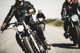 Three men wearing leather jackets riding cafe racer motorcycles along rural road.の写真素材 [FYI02859697]