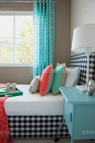 Coral and seafoam green decor on gingham bedの写真素材 [FYI02859703]