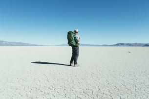 Male backpacker hiking in vast desert, Black Rock Desert, Nevadaの写真素材 [FYI02859722]