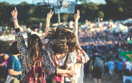 Rear view of three young women standing side by side at a summer music festival wearing feather headの写真素材 [FYI02859725]