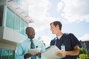 doctor and technician comparing notes outsideの写真素材 [FYI02859730]