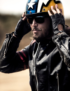 Bearded man wearing black leather jacket and sunglasses adjusting his yellow open face crash helmet.の写真素材 [FYI02859734]