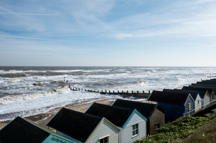 Seascape over a row of wooden beach huts, with waves rolling onto beach near groyne.の写真素材 [FYI02859747]