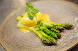 Close up high angle view of green asparagus with Hollandaise sauce and a poached egg on a plate.の写真素材 [FYI02859758]