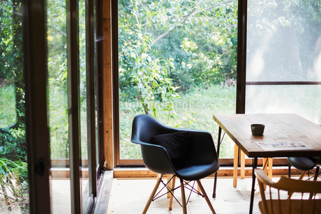 Interior view of residential building with black chair and wooden table, glass walls.の写真素材 [FYI02859766]