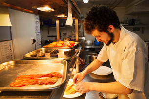 Chef standing in a restaurant kitchen at a counter plating food, trays with bacon, Black Pudding andの写真素材 [FYI02859778]