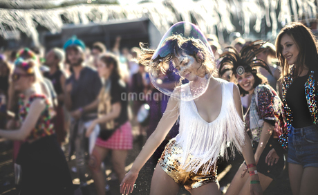 Young woman at a summer music festival wearing golden sequinned hot pants, dancing among the crowd.の写真素材 [FYI02859791]