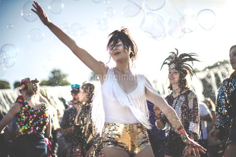 Young woman at a summer music festival wearing golden sequinned hot pants, dancing among the crowd.の写真素材 [FYI02859799]