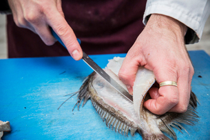 High angle close up of fishmonger filleting John Dory fish with knife on blue chopping board.の写真素材 [FYI02859812]