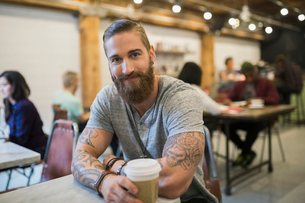 Portrait confident bearded man with tattoos drinking coffeeの写真素材 [FYI02859820]