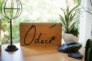 Close up of wooden sign, flowerpot, stones and ornament on a wooden table.の写真素材 [FYI02859821]
