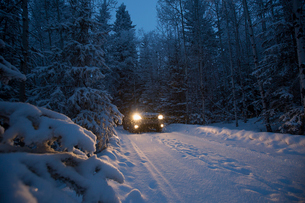 Truck with headlights driving on remote snow covered road in woodsの写真素材 [FYI02859832]