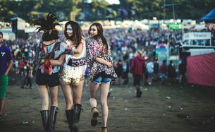 Rear view of three young women at a summer music festival wearing hot pants and Wellington boots, feの写真素材 [FYI02859846]