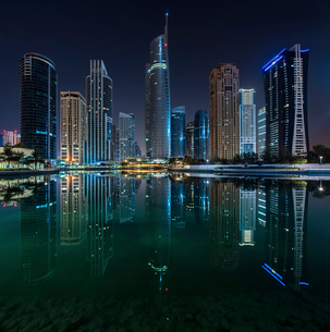 Cityscape of Dubai, United Arab Emirates at night, with illuminated skyscrapers lining the waterfronの写真素材 [FYI02859850]