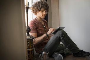 Loft living. A man sitting by a window using a digital tablet.の写真素材 [FYI02859869]