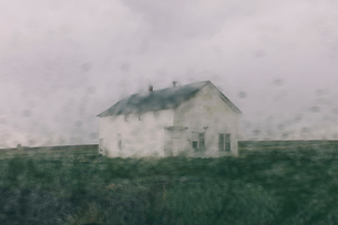 Abandoned farmhouse in a rainstorm, seen through a wet window. Blurred image.の写真素材 [FYI02859884]