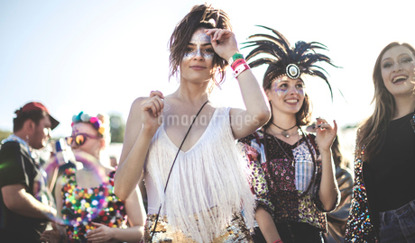 Two smiling young women at a summer music festival face painted, wearing feather headdress, standingの写真素材 [FYI02859891]