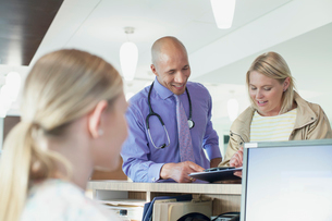 doctor and patient reviewing patient chart at nurses deskの写真素材 [FYI02859892]
