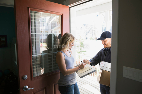 Woman signing for delivery at front doorの写真素材 [FYI02859921]