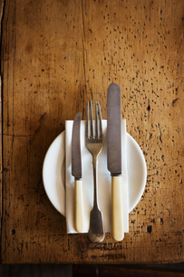 Close up high angle view of plate with knives and fork and a serviette on a rustic wooden table.の写真素材 [FYI02859922]