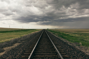Train tracks through prairie and farmland, storm clouds in distanceの写真素材 [FYI02859944]