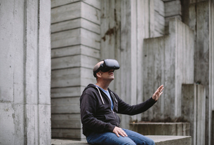 A middle aged man wearing a virtual reality headset.の写真素材 [FYI02859945]