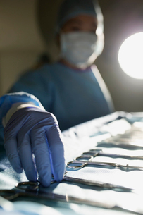 Plastic surgeon reaching for surgical scissors operating roomの写真素材 [FYI02859946]