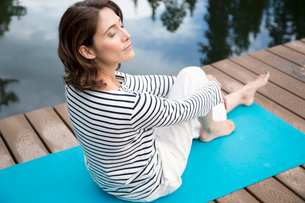 middle-aged woman meditating on yoga mat outdoorsの写真素材 [FYI02859961]