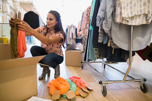 Business owner unpacking new inventory in clothing shopの写真素材 [FYI02860007]