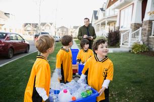 Coach and boys sports team gathering recycling neighborhoodの写真素材 [FYI02860017]