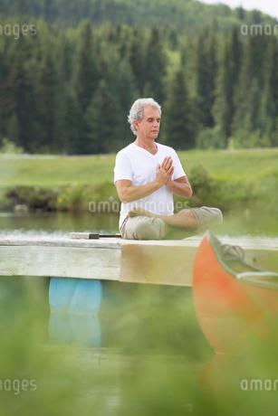 senior man meditating in lotus position on deckの写真素材 [FYI02860119]