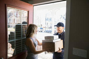 Woman receiving delivery at front doorの写真素材 [FYI02860174]
