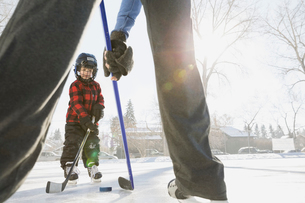 Father and son playing ice hockey on rinkの写真素材 [FYI02860223]