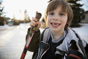 Portrait enthusiastic gap toothed boy holding ice hockey stick and ice skates on snowy roadの写真素材 [FYI02860244]