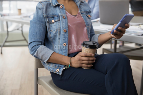 Businesswoman drinking coffee and texting with cell phone in officeの写真素材 [FYI02860250]