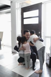 Children greeting businessman father at front doorの写真素材 [FYI02860305]