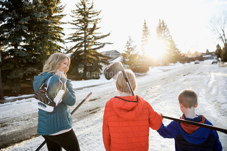 Mother and sons with ice hockey sticks and ice skates on sunny, snowy roadの写真素材 [FYI02860309]