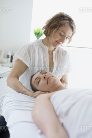 Female masseuse massaging neck of woman on spa massage tableの写真素材 [FYI02860320]