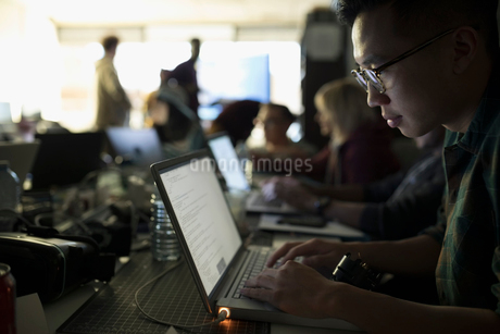Focused male hacker working hackathon at laptop in dark officeの写真素材 [FYI02860394]