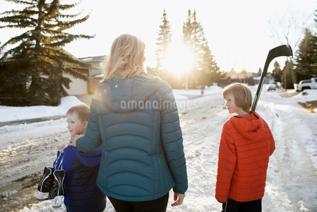 Mother and sons with ice hockey stick and ice skates on sunny, snowy roadの写真素材 [FYI02860412]