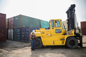 Male worker with clipboard leaning on forklift in sunny industrial container yardの写真素材 [FYI02860415]