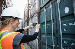 Female Caucasian worker with camera phone photographing shipping container in industrial container yの写真素材 [FYI02860461]