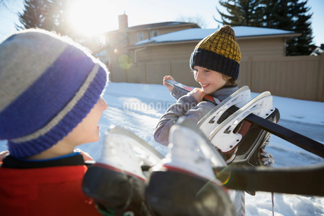 Smiling boys with ice hockey sticks and ice skates on sunny snowy roadの写真素材 [FYI02860462]