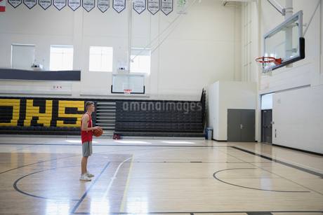 Male college basketball player practicing free throws in gymnasiumの写真素材 [FYI02860482]
