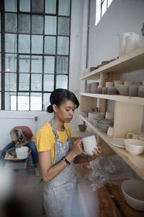 Female potter drying clay pitcher on shelf in art studioの写真素材 [FYI02860486]