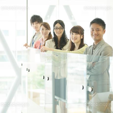 オフィスで微笑むビジネスウーマンとビジネスマンの写真素材 [FYI02860497]
