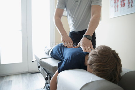 Male physiotherapist examining back of boy in clinic examination roomの写真素材 [FYI02860572]