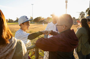 Baseball player fist bumping friend at sunny fenceの写真素材 [FYI02860834]