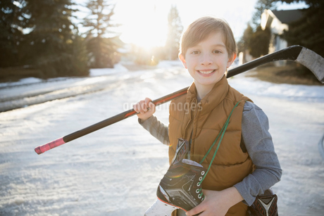 Portrait smiling boy holding ice hockey stick and ice skates on sunny, snowy roadの写真素材 [FYI02860835]